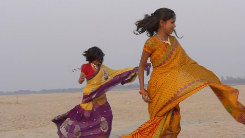 Indian young women dancing near the Ganges river in the vicinity of Varanasi city, march 2015