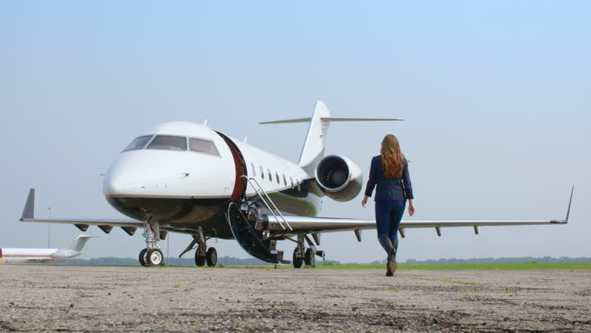 Attractive brunette in a blue jacket and jeans walking towards an executive jet at an airfield.  Wide view, originally recorded in slow motion 4K at 60fps.