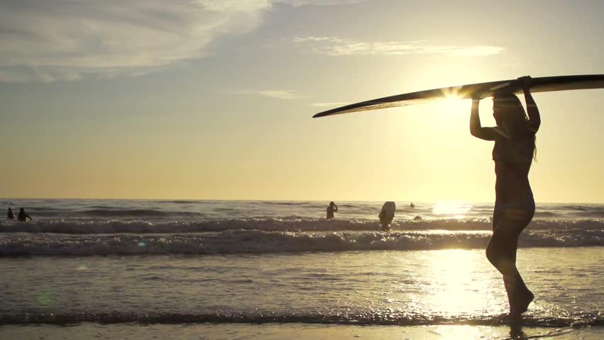Silhouette Surfer Girl Walking On Beach at Sunset In Slow Motion  - HD stock video clip