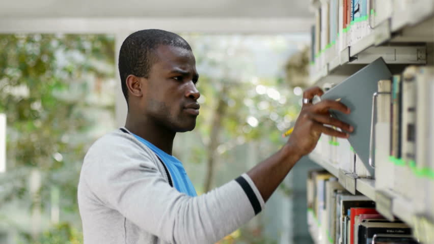 African american male college student taking book from shelf in library and looking at camera. Man, people, education