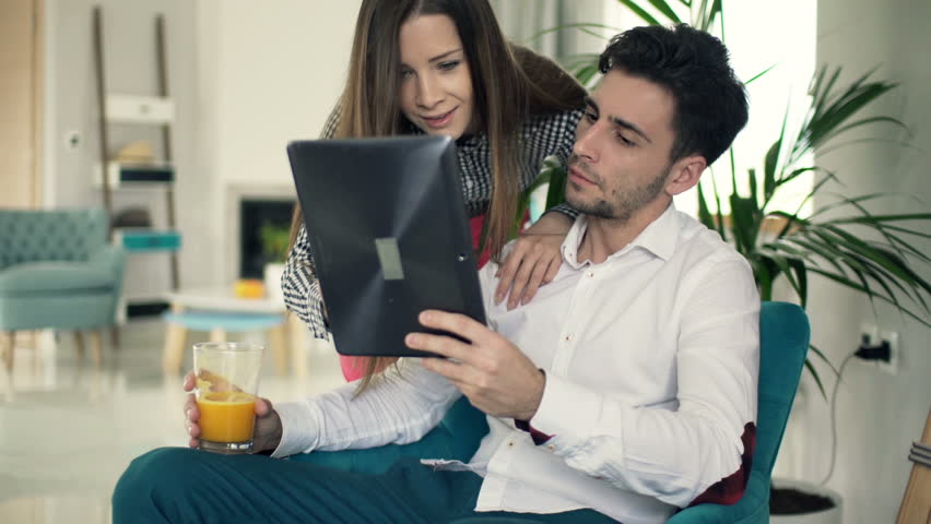 Young couple talking and using tablet computer at home
