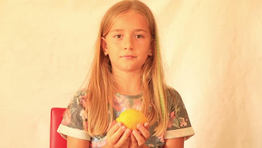 Cute girl eating lemon