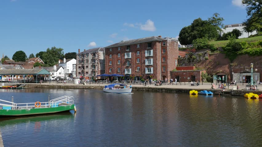 Exeter, Devon, UK  August 18th 2015: The waterfront on Exeter Quay, Exeter Canal tour boat, also with people rowing and canoeing. - 4K stock footage clip