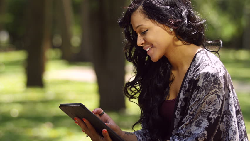 A young woman using her ipad outdoors in a park   Shutterstock HD Video #11386358