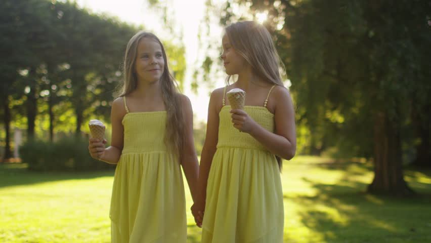 Two Girls are Walking at Park and Holding Ice Cream in Hands. Shot on RED Cinema Camera in 4K (UHD). | Shutterstock HD Video #11396492