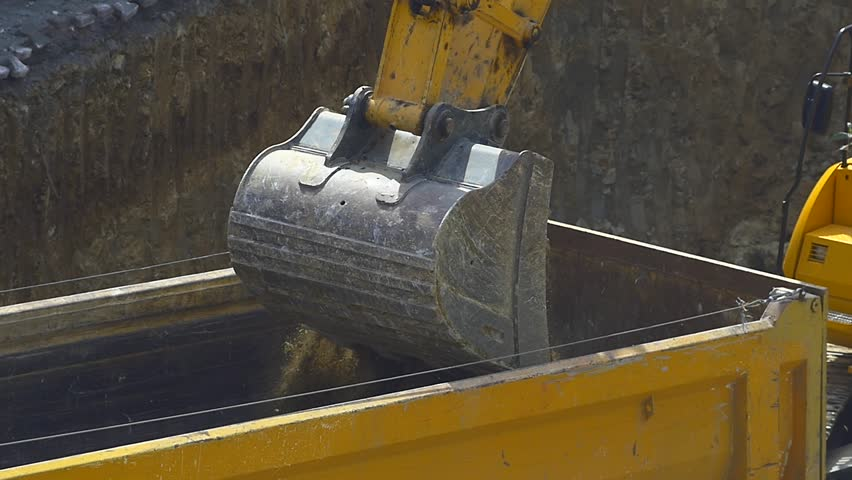 Slow motion - Excavator loading soil on a dump truck. Crawler dozer and tipper working at the construction site. Close up video.