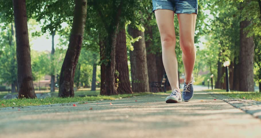 Female feet in sneakers gumshoes walking and posing on a park road, close up. Woman's feet in denim sports shoes passing by the camera. Slow motion, 120fps. 4K, DCi.
