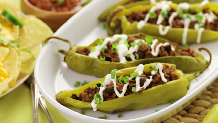 Chipotle beef & bean stuffed chili peppers garnished with sour cream ...