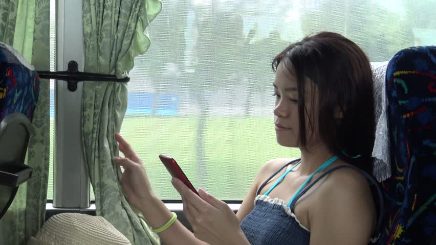 Asian Woman Used Touchscreen Tablet Smartphone Device, Young woman watching video on touchpad, then choosing another one during day ride in the bus, 4K -Dan | Shutterstock HD Video #11435066