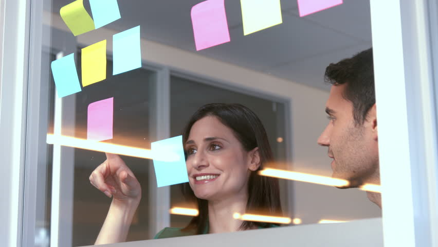 Casual business people looking at post it in office - 4K stock footage clip