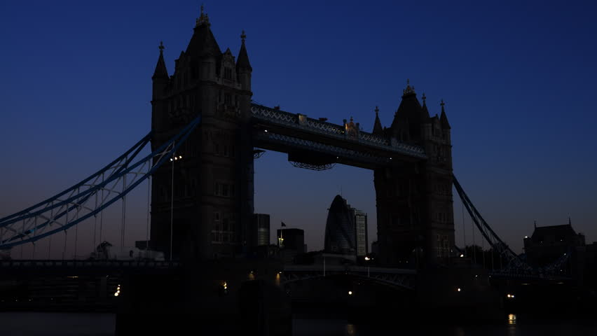 Very clear sunrise in London, England. The River Thames' most famous crossing, Tower Bridge, is gradually lit by the sun. Vehicles pass across the road bridge.