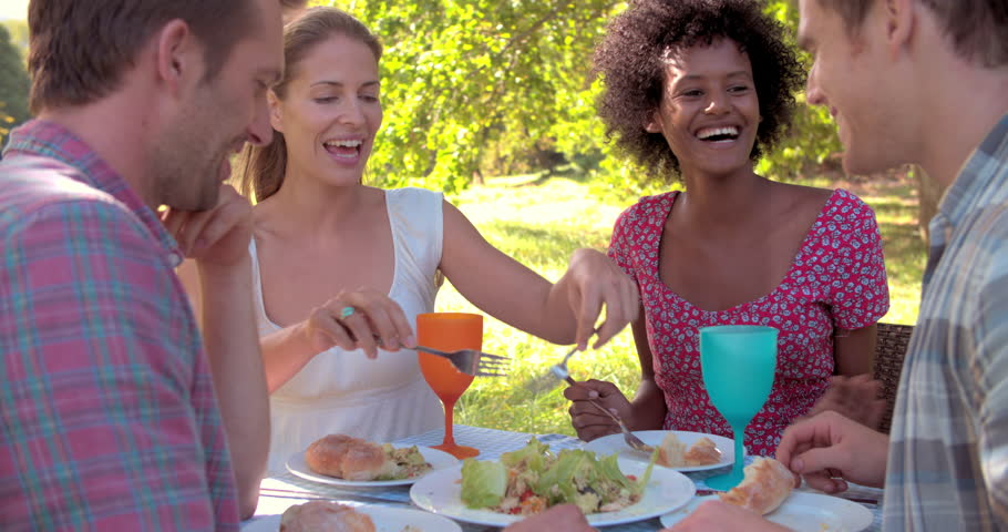 Four friends eating at a table together outdoors
