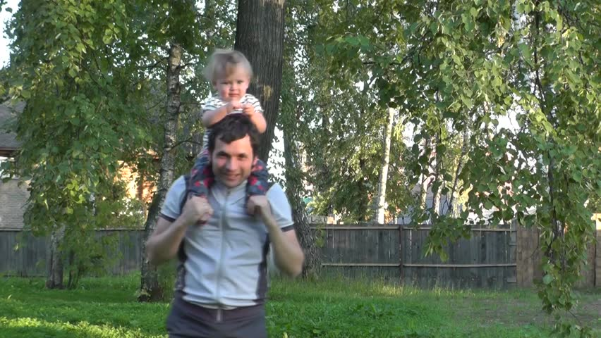 Dad holds his daughter in arms. Father playing with baby. Male babysitter crouches with happy child. On sunny summer evening. Green Park. - HD stock video clip