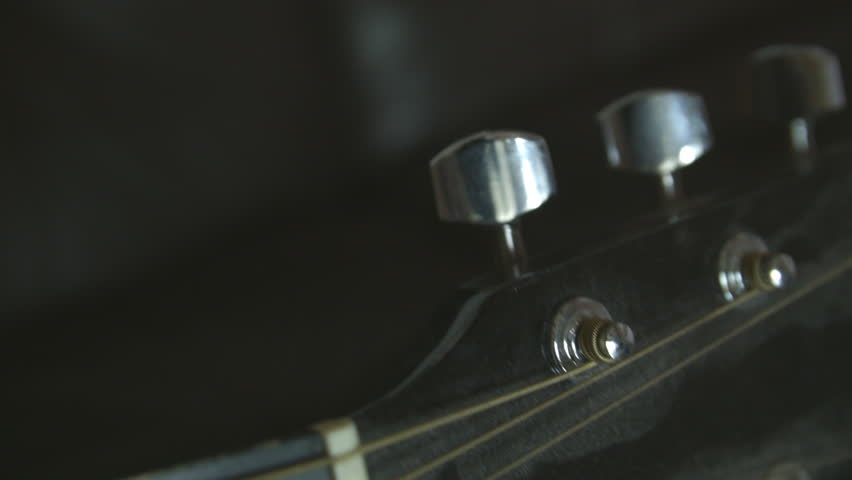Hand tuning a classical guitar HD stock footage. Close shot of a male hand tuning a classical guitar. ProRes.