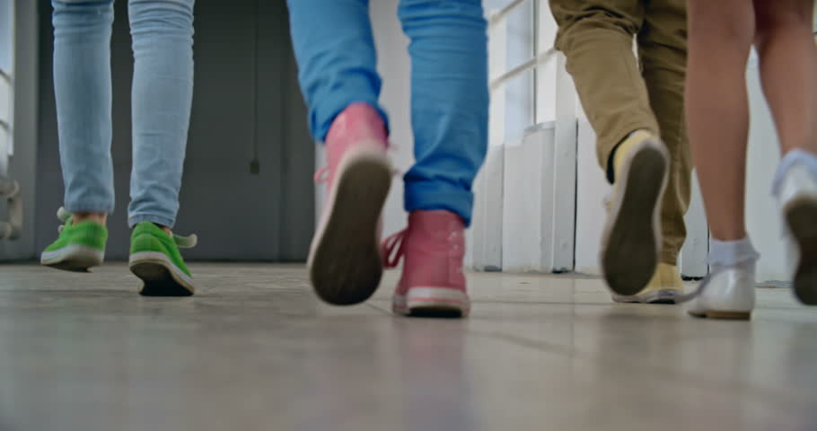 Low angle view of elementary students leaving school corridor  - 4K stock footage clip