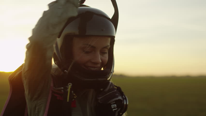 Girl Skydiver in Helmet is Picking Up Parachute after Successful Landing. Shot on RED Cinema Camera in 4K (UHD).