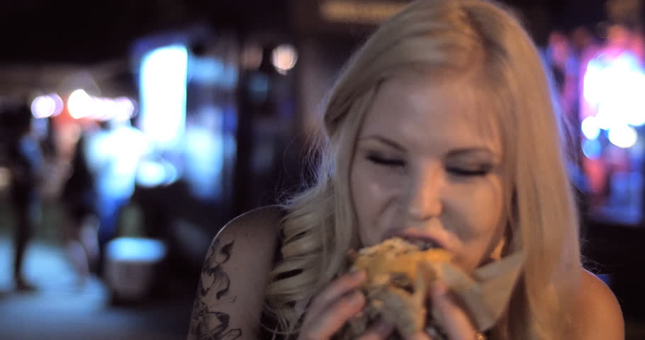 4K - A Close up shot of pretty hipster hip cool fun girl eating late night burger from a popular trendy food truck in a urban street festival setting at night.  Version 1 - shorter | Shutterstock HD Video #11610485