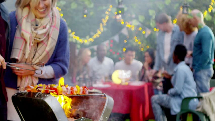 Happy couple share a kiss at bbq while friends socialize in the background. Shot on RED Epic.