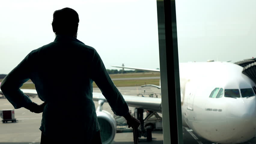Man looking at plane in the airport  - 4K stock video clip
