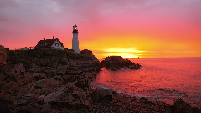 Establishing aerial shot of a gorgeous sunrise in Maine capturing a Lighthouse. Vivid colors of purples, pinks and yellows are reflected in the water. #11664980