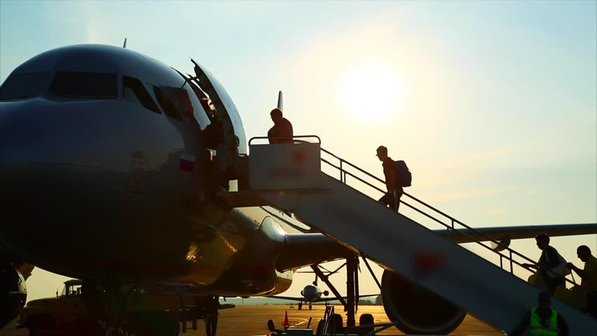 People climb the ladder into the plane, airport