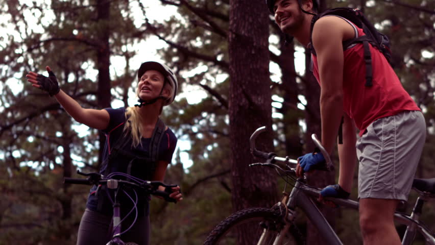 Couple biking through a forest in slow motion