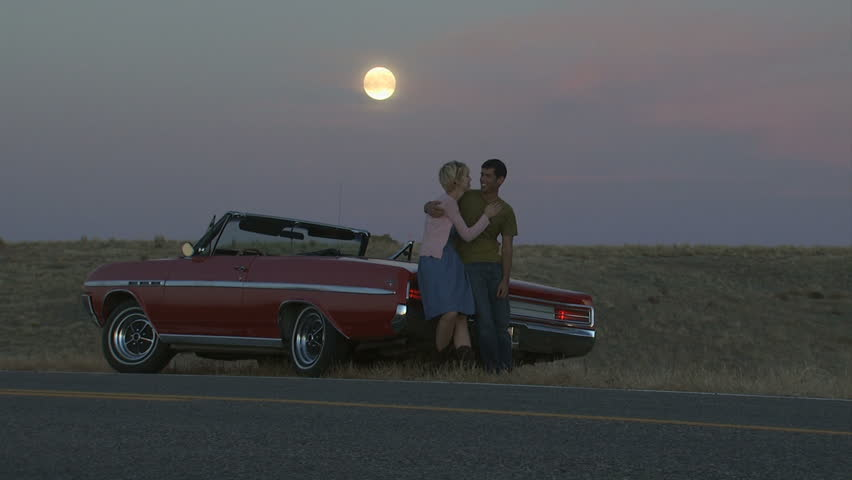 couple on the side of the road in a convertible