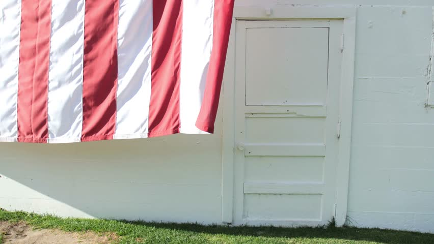 A large American flag blows in the wind on an old white barn. - 4K stock video clip