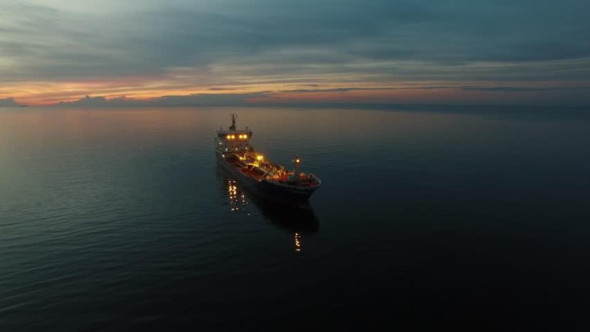 Aerial Orbit Shot of Tanker Ship Moving in Sea at Night.