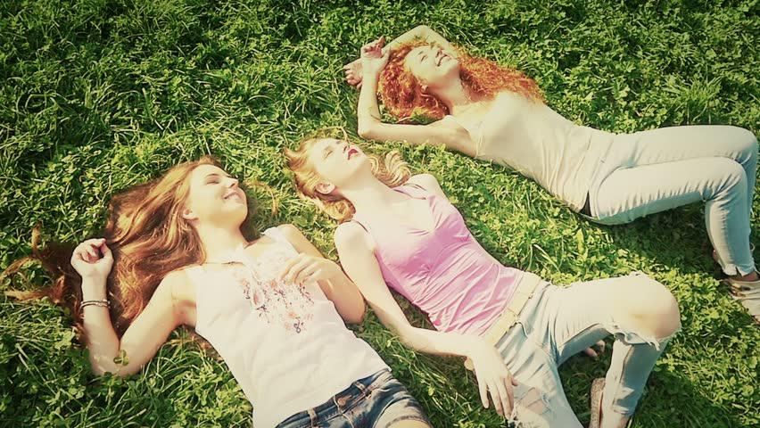 Three friends, young pretty girls, caucasians, having fun outdoors in nature, laying on grass, slow motion, high angle. - HD stock video clip
