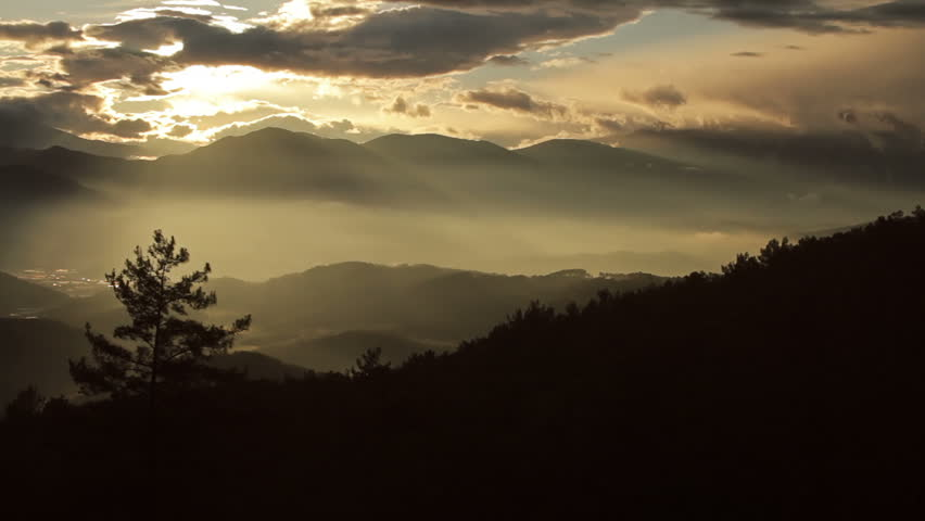 Mountains and sun behind clouds, timelapse - HD stock video clip