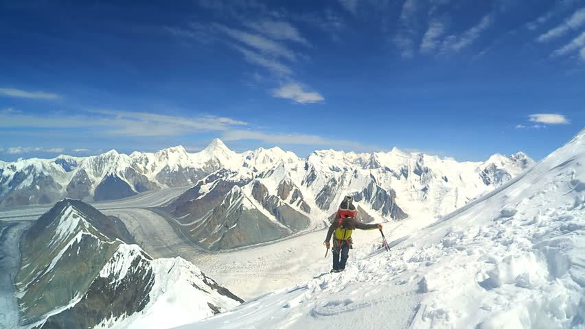 Mountaineer reaches the top of a snowy mountain - HD stock video clip
