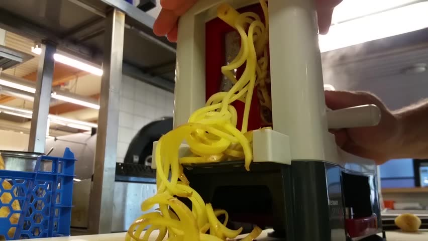 Making homemade cranked potato fries, at a restaurant kitchen - HD stock video clip