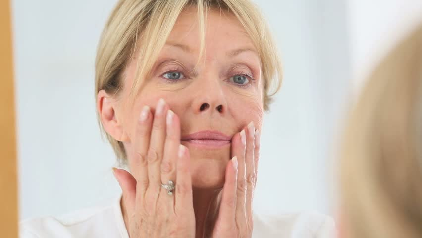 Senior woman applying cosmetic lotion on her face