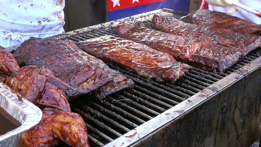 Pork Side Ribs Cooking On A Large Commercial BBQ Outdoors At A Rifest Event. Ribs Are A Popular Summer Food In North America.