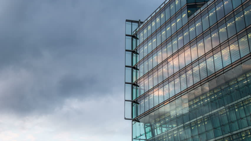 BERLIN, GERMANY – June 15, 2015: cloudy sky with modern illuminated reflected glass  facade timelapse
