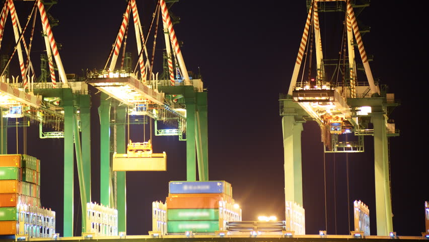 Time-lapse footage with pan left motion of industrial cranes loading containers onto container ship at a shipyard in port of Los Angeles at night