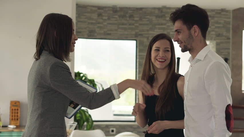 Real estate agent giving keys of new home to happy couple