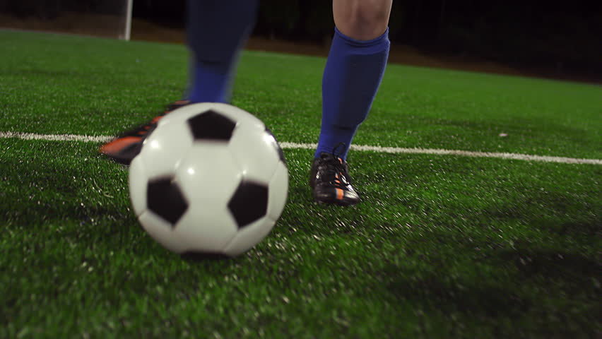 A female soccer player dribbles down the field at night while her opponents slide tackle and defend - 4K stock footage clip