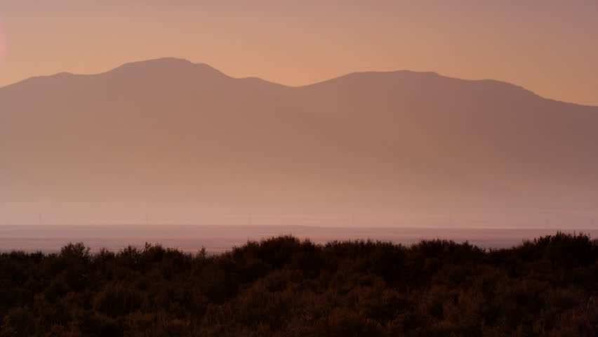 Nevada Desert - May 2013: Slow motion shot of group of cowboys riding horses. Mountains are visible in background. Shot at dusk.