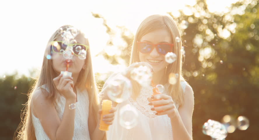 Family blowing bubbles in the sunlight at sunset in the park - 4K stock footage clip