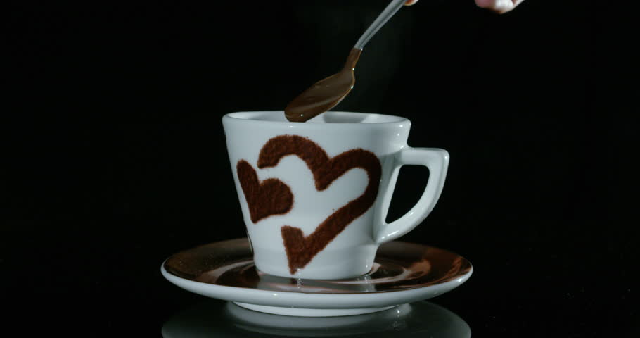 Super slow motion still life of young man hand mixing with a small metal spoon hot chocolate in white porcelain mug with hearts design isolated on a black background in 4k (close up)