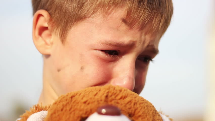 dirty orphan boy close-up crying and petting a stuffed toy wipes the tears on the background of the  ruins