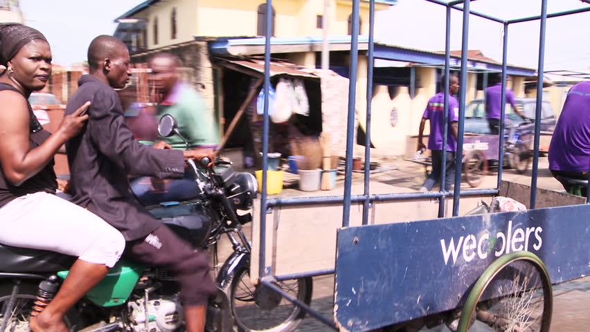 LAGOS, NIGERIA - CIRCA MAY 2014: Street scene. Commuters and 'Wecyclers' bicycles. 1080p HD. - HD stock video clip