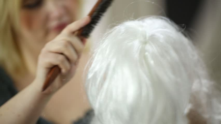 Visagiste combs white artificial curly wig in studio.