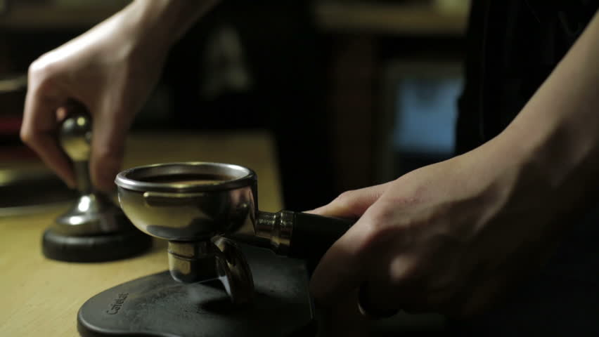 Barista tamping the grind coffee for espresso. - HD stock footage clip