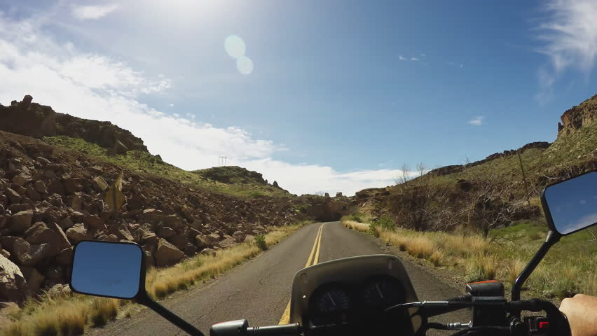 Point of view vehicle driving shot overlooking handlebars of a motorcycle. Biker motorcyclist rides on a narrow curving canyon road in 4K format. | Shutterstock HD Video #12079214
