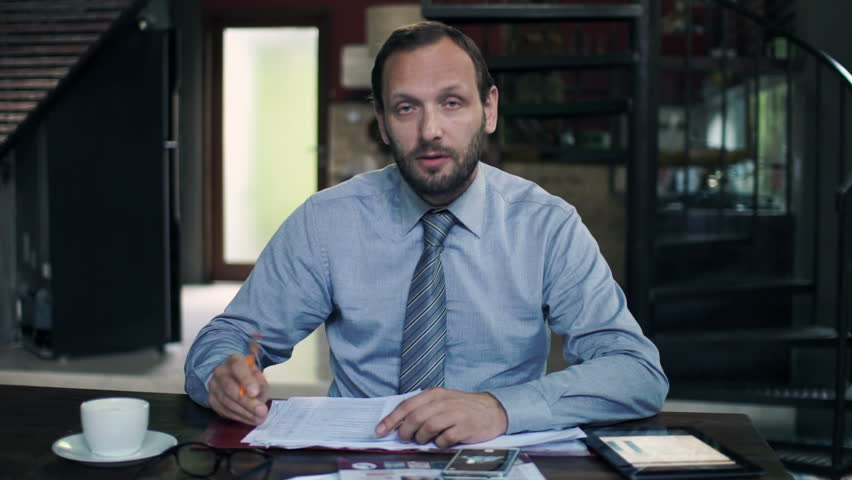 Friendly businessman with documents talking good news to camera at home  - HD stock video clip