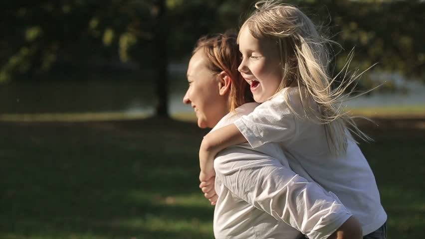 Daughter riding on mother in a city park at sunset. Slow motion   Shutterstock HD Video #12096125