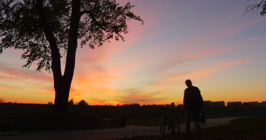 Man with Backpack is Leaving by Bicycle, Man's Silhouette at Sunset, Woman with Baby Pram is Walking to the Other Side ,Woman's Back, Silhouette, Buildings on a Horizon, footpath in park, Sunset,